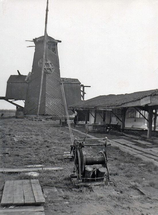 De Gekroonde Poelenburg <br>(De Poelenburg), Zaandam, De Poelenburg wordt gedemonteerd voor verplaatsing naar de Zaanse Schans. Het bovenwiel wordt met een mast uitgetakeld; de bovenas ligt links voor de borst op de grond.  Foto: n.n. (1963), coll. Arie Hoek.